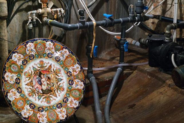 il piatto raffaellesco di La Vecchia Faenza collocato fra gli ingranaggi della Fontana Monumentale di Faenza