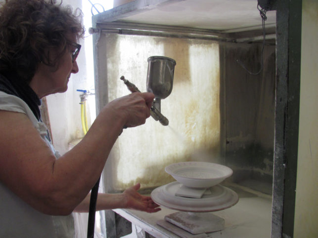 The ceramist sprays the crystalline before baking the pottery